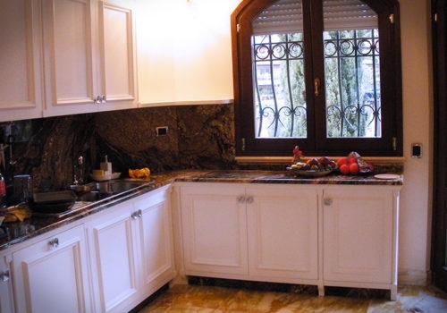 Cucina laccata con cornici riportate con finestra centinata in rovere lamellare trattata con vernici per esterni