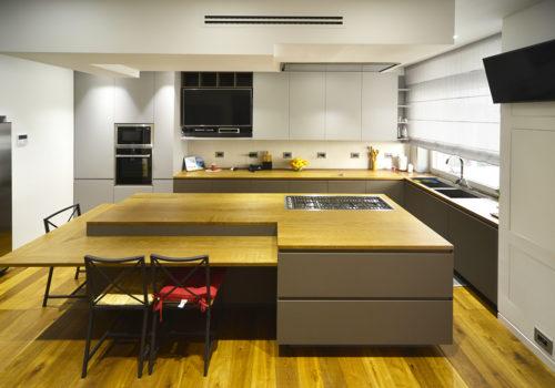 Cucina laccata satinata con finitura touch soft bicolore, con isola centrale e ripiani in rovere tinto noce spazzolati a poro aperto