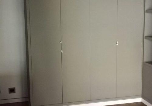 Camera studio con armadio e letto matrimoniale a scomparsa laccata grigio opaco