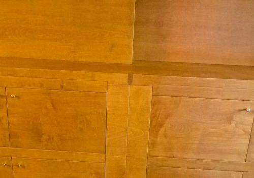 Libreria impiallicciata in acero color miele con sportello scorrevole a copertura televisore