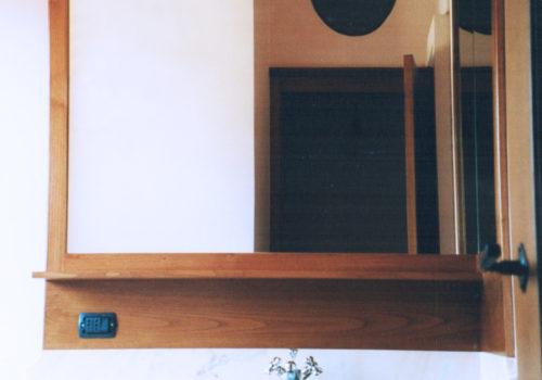 Mobile bagno in castagno tinto noce con sportello centinato e bugnato e specchiera con ripiani centinati