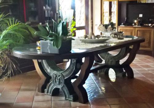 Tavolo in castagno centinato con piano incassato in cristallo e doppia gamba sagomata in legno e marmo